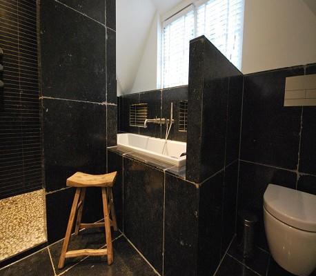 Badkamer met grote zwarte tegels